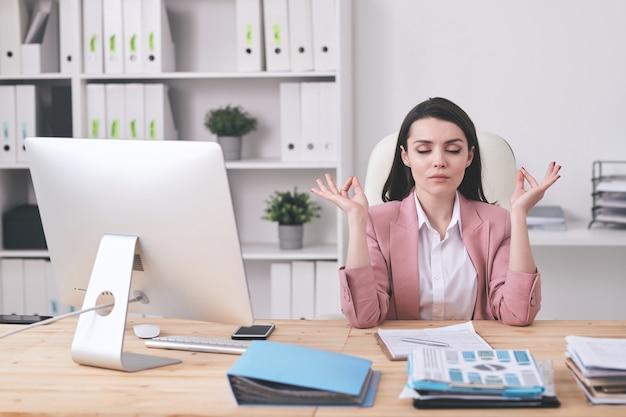 Jonge brunette zakenvrouw met gesloten ogen vingers aan te raken tijdens het vinden van zen op de werkplek
