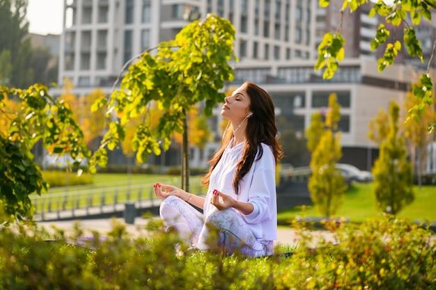Jonge brunette zit op gras op de achtergrond van het stadspark, ontspan met muziek in oortelefoons in yoga lotuspositie met handen op knieën