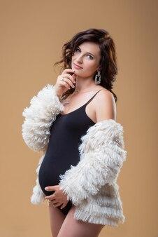 Jonge brunette zwangere vrouw in bontjas op een effen muur mooie stijlvolle gezonde zwangerschap