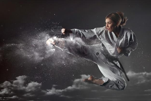 Jonge brutale emotionele karate meisje in een pak springt op en maakt een krachtige slag. ongebreideld energieconcept. vechtsporten