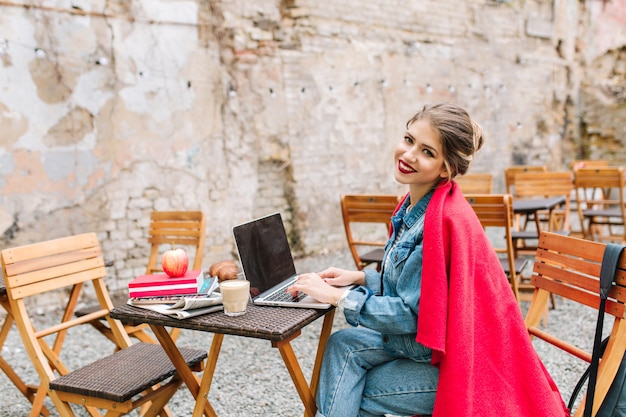 Jonge buisnesswoman bezig met het nieuwe project met laptop tijdens de lunch op het terras.