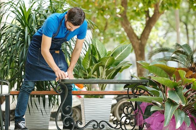 Jonge buitencafé-kelner die tafels schoonmaakt met desinfecterend reinigingsmiddel voor opening