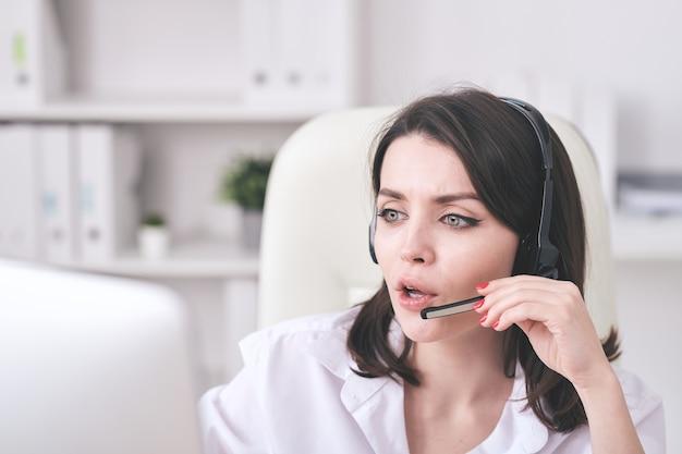 Jonge call centreexploitant die in microfoonhoofdtelefoon online vraag beantwoordt en informatie op computermonitor controleert