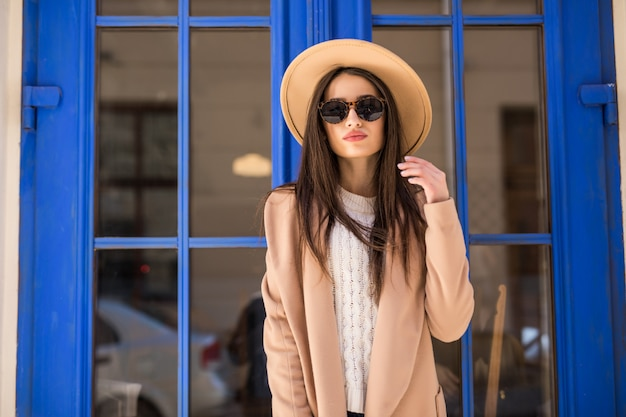 Jonge casual geklede dame in heldere vacht hoed en zonnebril staat voor blauwe deur