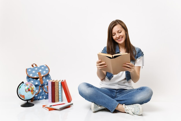 Jonge casual glimlachende vrouw student in denim kleding met boek lezen zittend in de buurt van globe, rugzak, schoolboeken