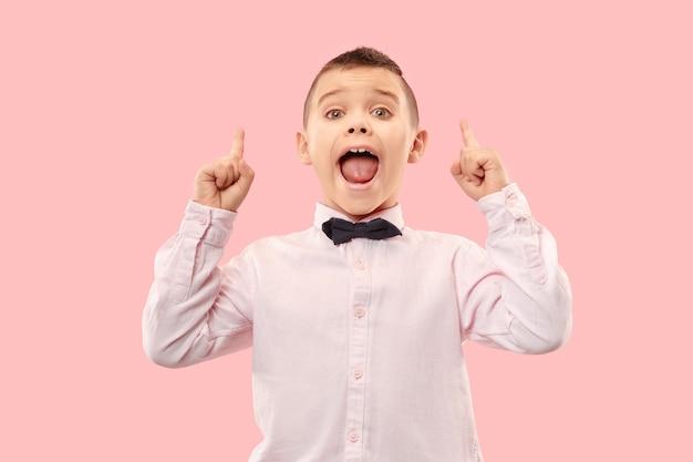 Jonge casual jongen schreeuwen. roepen. huilende emotionele tiener die op roze studioachtergrond gilt. het mannelijke portret van halve lengte.