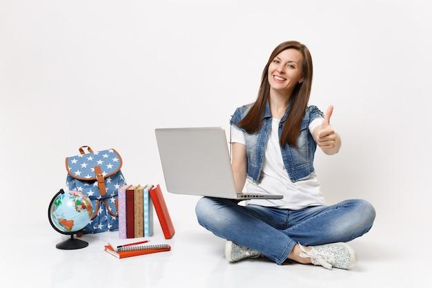 Jonge casual lachende vrouw student bedrijf gebruik laptop pc-computer met duim omhoog zittend in de buurt van globe, rugzak, schoolboeken geïsoleerd
