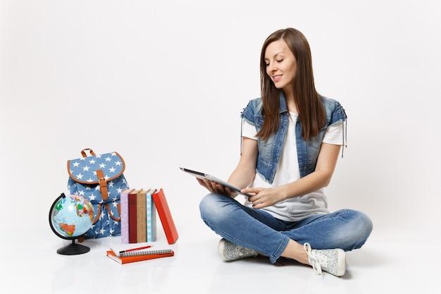 Jonge casual lachende vrouw student in denim kleding houden met behulp van tablet pc-computer zitten in de buurt van globe rugzak schoolboeken geïsoleerd