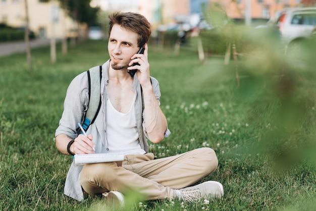 Jonge casual man met behulp van een slimme telefoon sms-berichten in de straat tijdens het studeren