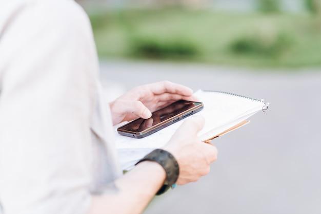 Jonge casual man met behulp van een slimme telefoon sms-berichten in de straat