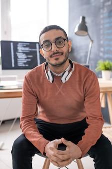 Jonge casual programmeur met koptelefoon op zoek naar jou zittend met werkplek