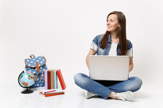 Jonge casual slimme vrouw student bedrijf met behulp van laptop pc-computer opzij kijken zittend in de buurt van globe, rugzak, schoolboeken geïsoleerd