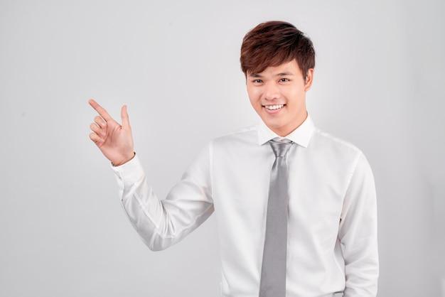 Jonge casual student wijst met de vinger naar de andere kant op een witte achtergrond