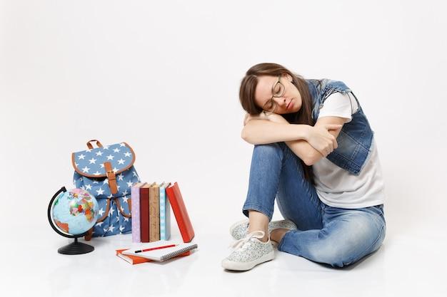 Jonge casual vermoeide, ontspannen vrouw student in denim kleding bril slapen zittend in de buurt van globe, rugzak, schoolboeken geïsoleerd