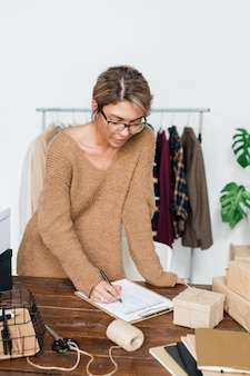 Jonge casual vrouw permanent door houten tafel en het controleren van de lijst met bestelde artikelen na ontvangst van pakket van online winkel