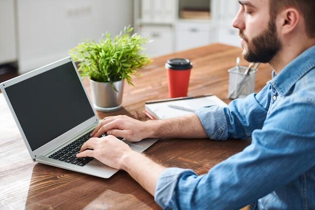 Jonge casual zakenman typen op laptop toetsenbord door tabel tijdens het invoeren van informatie in de database of het plannen van werkzaamheden