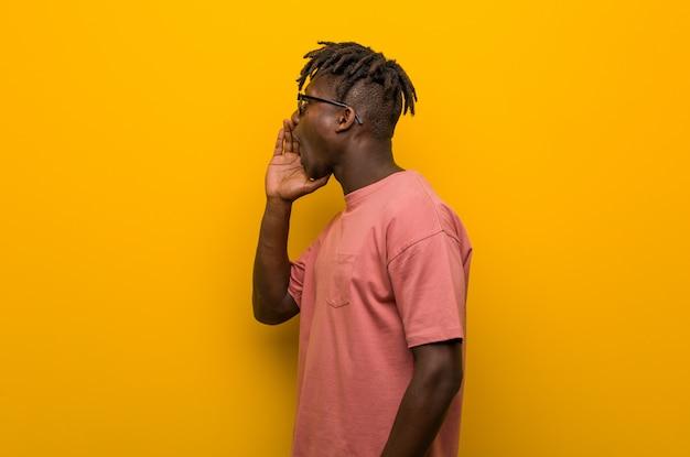 Jonge casual zwarte man draagt een zonnebril schreeuwen en houden palm in de buurt van geopende mond.