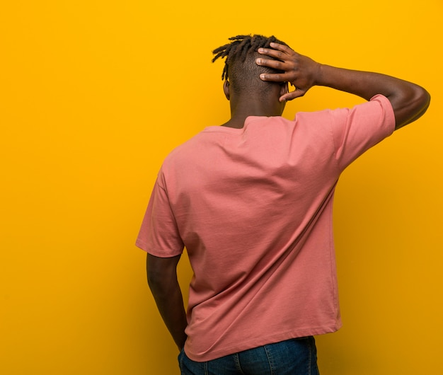 Jonge casual zwarte man draagt een zonnebril van achter na te denken over iets.