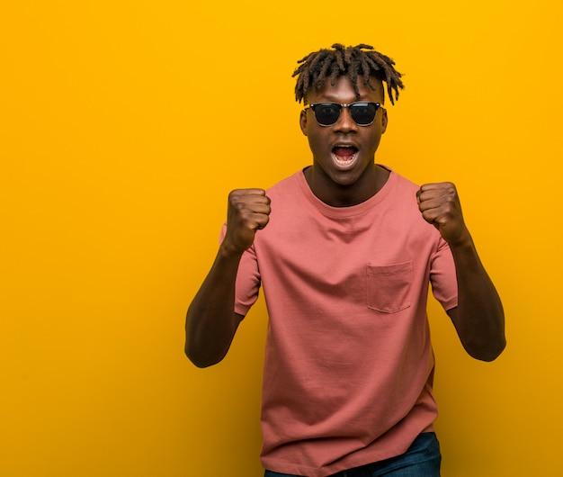 Jonge casual zwarte man draagt een zonnebril zorgeloos en opgewonden juichen. zege .
