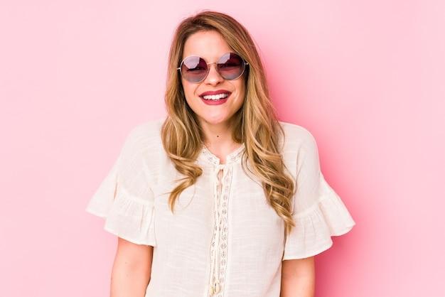 Jonge caucian vrouw met bril geïsoleerd op roze muur lacht en sluit de ogen, voelt zich ontspannen en gelukkig.