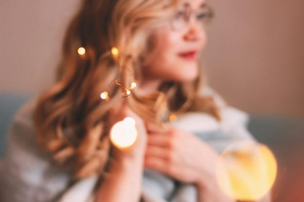 Jonge charmante blondevrouw in glazen met lichten in haar haar