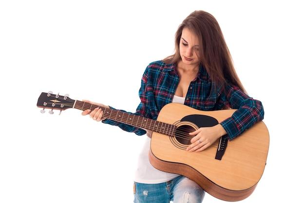 Jonge charmante brunette met gitaar in handen geïsoleerd op witte achtergrond