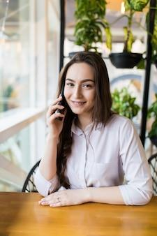Jonge charmante vrouw bellen met mobiele telefoon zittend alleen in de coffeeshop in vrije tijd, aantrekkelijke vrouw met schattige glimlach met pratend gesprek met mobiele telefoon terwijl rust in café