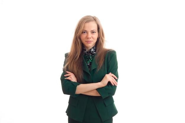 Jonge charmante vrouw in een groen jasje legde haar handen in elkaar en keek naar camera geïsoleerd op een witte muur