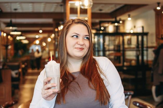 Jonge charmante vrouw plus grootte met milkshake in hand in café, enjoing leven en uiterlijk