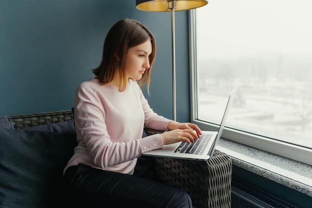 Jonge charmante vrouwelijke freelancer die laptop computer voor afstandsbaan met behulp van