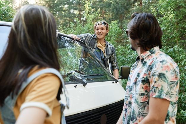 Jonge chauffeur praat met jong stel en vraagt de weg tijdens zijn reis