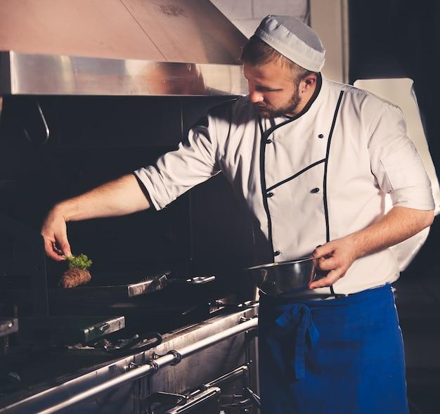 Jonge chef-kok bereidt vlees in het keukeninterieur
