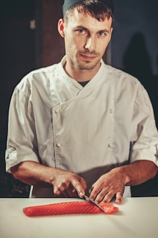 Jonge chef-kok coock gekleed in witte uniform gesneden zalm vis op tafel in restaurant. hij werkt aan sashimi. traditionele japanse sushi bereiden in het interieur van de moderne professionele keuken
