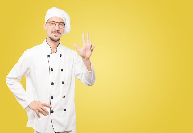 Jonge chef-kok die een gebaar drie maakt