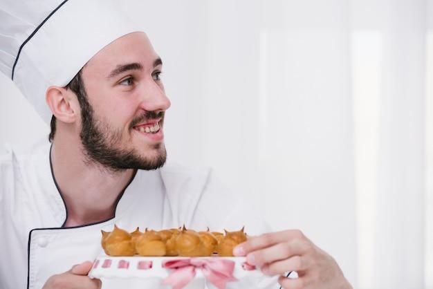 Jonge chef-kok die met schuimgebakje weg kijkt