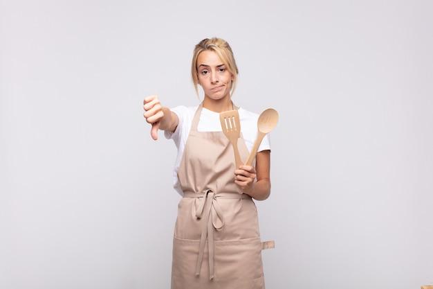 Jonge chef-kok die zich boos, boos, geïrriteerd, teleurgesteld of ontevreden voelt, duimen naar beneden toont met een serieuze blik