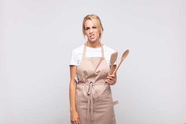 Jonge chef-kok die zich verbaasd en verward voelt, met een domme, verbijsterde uitdrukking die naar iets onverwachts kijkt