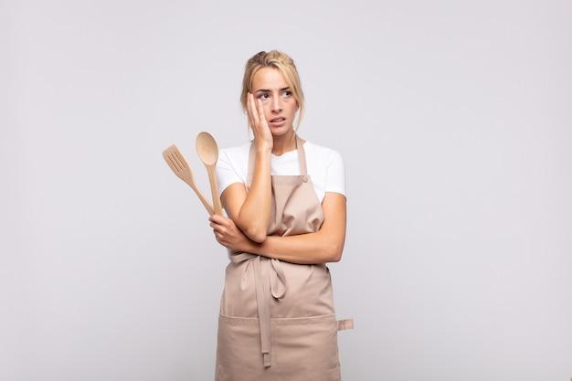 Jonge chef-kok die zich verveeld, gefrustreerd en slaperig voelt na een vermoeiende, saaie en vervelende taak, gezicht met de hand vasthouden