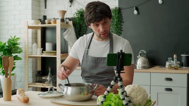 Jonge chef-kok in een schort die zichzelf filmt voor een kookblog terwijl hij in de keuken een gezonde maaltijd met groenten kookt