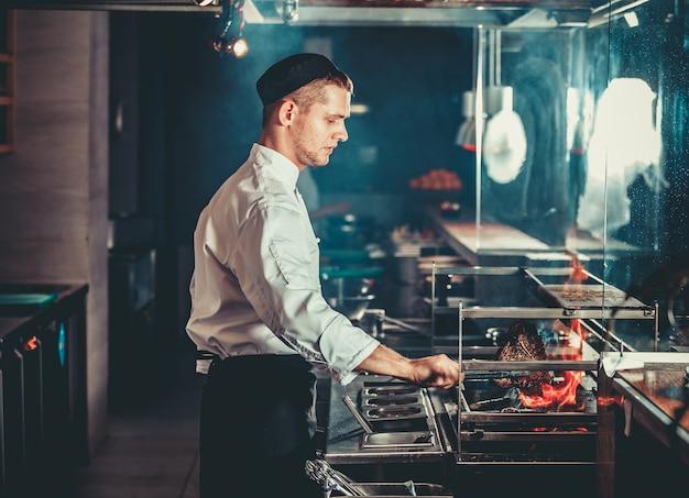Jonge chef-kok in wit uniform kokend vlees