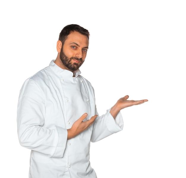Jonge chef-kok in wit uniform zonder hoed geïsoleerd op een witte muur.