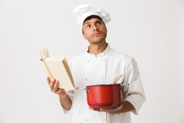 Jonge chef-kok man geïsoleerd op een witte muur koken.