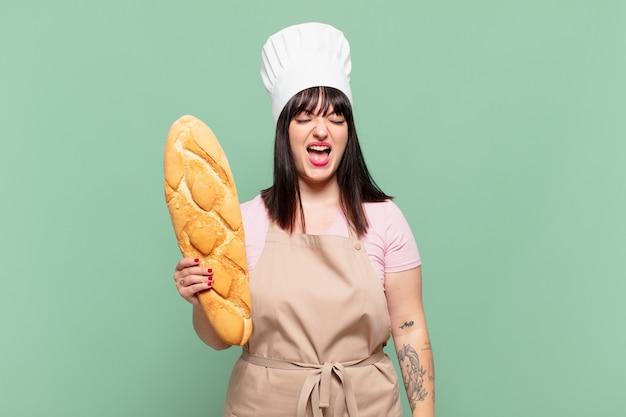 Jonge chef-kokvrouw die agressief schreeuwt, erg boos, gefrustreerd, verontwaardigd of geïrriteerd kijkt, nee schreeuwt