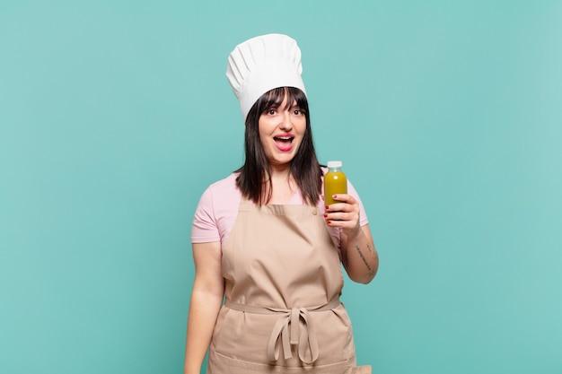 Jonge chef-kokvrouw die blij en aangenaam verrast kijkt, opgewonden met een gefascineerde en geschokte uitdrukking