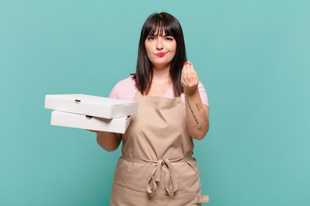 Jonge chef-kokvrouw die capice of geldgebaar maakt en u vertelt om uw schulden te betalen!
