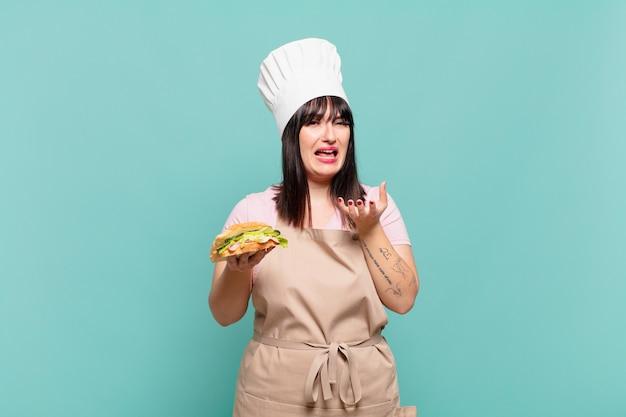 Jonge chef-kokvrouw die er wanhopig en gefrustreerd, gestrest, ongelukkig en geïrriteerd uitziet, schreeuwend en schreeuwend