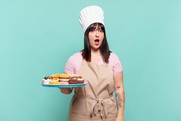 Jonge chef-kokvrouw die erg geschokt of verrast kijkt, starend met open mond en zegt wow