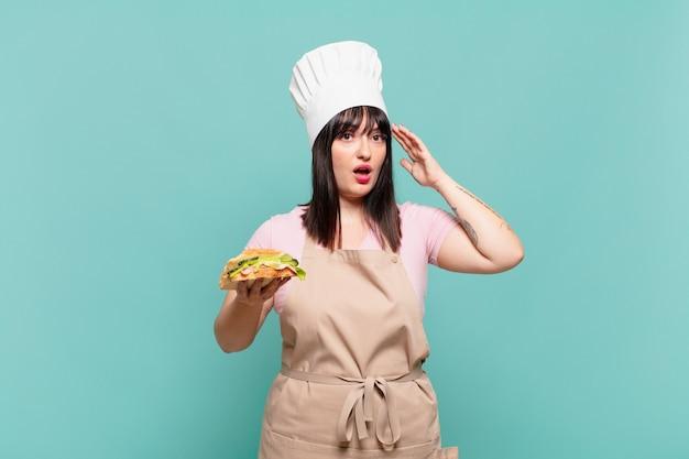 Jonge chef-kokvrouw die gelukkig, verbaasd en verrast kijkt, glimlacht en verbazingwekkend en ongelooflijk goed nieuws realiseert