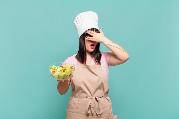 Jonge chef-kokvrouw die geschokt, bang of doodsbang kijkt, haar gezicht bedekt met de hand en tussen de vingers gluurt
