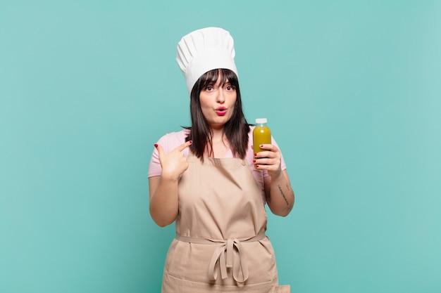 Jonge chef-kokvrouw die geschokt en verrast kijkt met wijd open mond, wijzend naar zichzelf